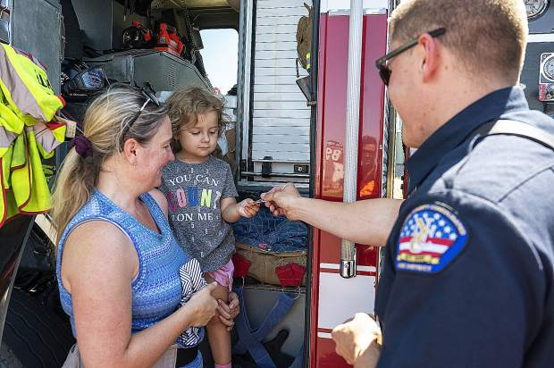 Branson Meyers, a firefighter for the Nevada County Consolidated Fire District, gives a fire sticker to Ariela Morgan and mother Glory Waschevski Saturday morning at the Grass Valley Airshow.