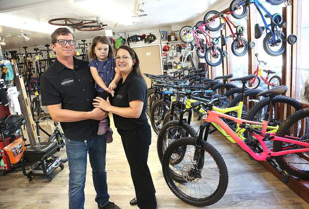 Cameron and Jessica hold their daughter Josephine while in Tour of Nevada City Bike Shop where the two met. Cameron is still employed by the cycle shop.