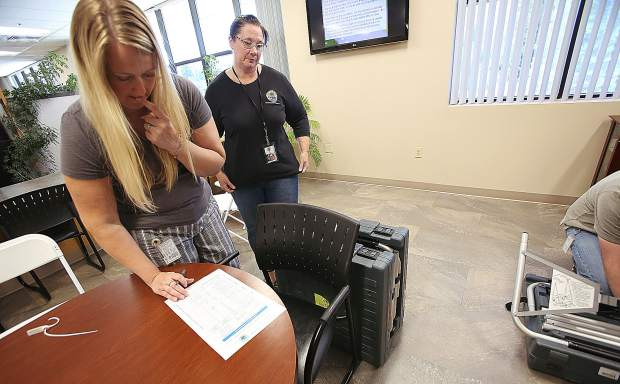 Nevada County Administrative Assistant Teal Caddy works off a checklist as the electronic voting booths are set up in advance of Monday's voting.