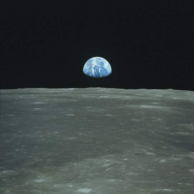 View of Moon limb with Earth on the horizon,Mare Smythii Region. Earth rise. This image was taken before separation of the LM and the Command Module during Apollo 11 Mission. Original film magazine was labeled V. Film Type: S0-368 Color taken with a 250mm lens. Approximate photo scale 1:1,300,000. Principal Point Latitude was 3 North by Longitude 85 East. Foward overlap is 90%. Sun angle is High. Approximate Tilt minimum is 65 degrees,maximum is 69. Tilt direction is West (W).