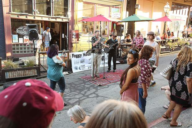 Folks gather along Commercial Street to hear performers such as Chris Olander in front of the Foggy Mountain Music stage during the First Friday Art Walk.