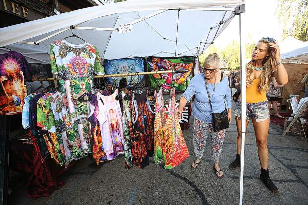 A pair of shoppers check out one of the many vendor booths with items on display and for sale during Friday's art walk in Nevada City.