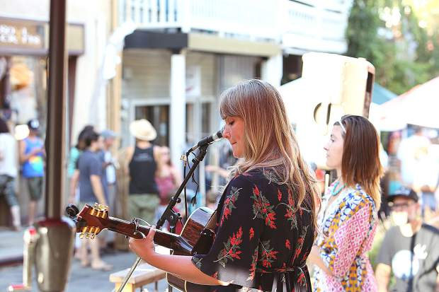 Musical duo Karen Woerner (left) and Cassidy Joy play their guitars and sing for folks along the Commercial Street Boardwalk during Friday's First Friday Art Walk in downtown Nevada City.