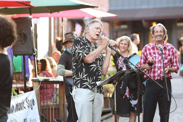 Nevada County Poet Laureate Chris Olander recites a poem while musicians play along on Commercial Street which was closed to vehicle traffic to allow for the Nevada City First Friday Art Walk.