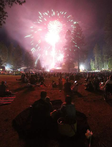 Families are illuminated as they watch the 2019 Fourth of July fireworks show from the lawns of the Nevada County  Fairgrounds Thursday evening.