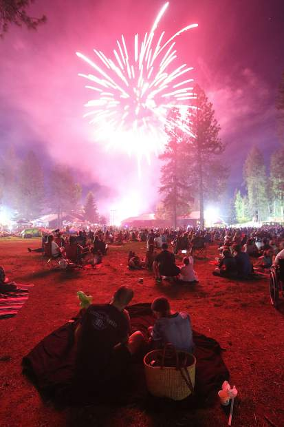 The lights of exploding fireworks illuminate the hundreds of families that took to the open fields of the Nevada County Fairgrounds to enjoy the Hats off to Nevada County Fourth of July fireworks show Thursday evening.