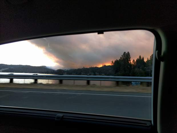 As a fmaily left their home on the hill on the far side of the lake near the smoke. this was their view looking back during the Lobo Fire. Today, community residents across the county are working to keep each other safe if catastrophe strikes again.