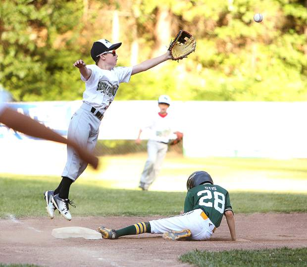 Sierra Foothills Little League All Star 3rd baseman Jonathan Cleek reaches for a throw while Auburn's Gavin Otis slides in safely during last week's matchup at Pioneer Park in Nevada City.