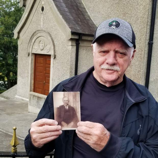 Francis McFadden holds a photograph of his grandfather, Edward McFadden, as Francis stands in front of a church in the Irish village where his grandfather was born. This photo was taken by Francis's wife, Louise, during their vacation in Ireland.
