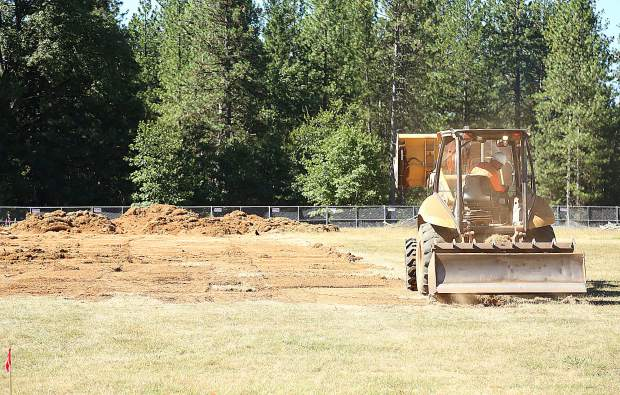 A construction worker breaks ground on the Lyman Gilmore synthetic turf field prior to Thursday evening's ceremonial ground breaking.