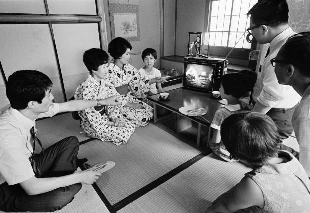 ADVANCE FOR USE SATURDAY, JULY 13, 2019 AND THEREAFTER-FILE - In this July 21, 1969 file photo, a family in Tokyo watches TV showing U.S. President Richard Nixon superimposed on a live broadcast of the Apollo 11 astronauts saluting from the moon. (AP Photo)