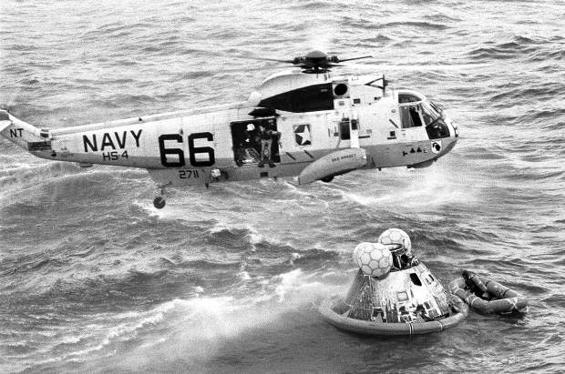 ADVANCE FOR USE SATURDAY, JULY 13, 2019 AND THEREAFTER-In this July 24, 1969 photo from the U.S. Navy, Navy UDT swimmer Clancy Hatleberg prepares to jump from a helicopter into the water next to the Apollo 11 capsule after it splashed down in the Pacific Ocean, to assist the astronauts into the raft at right. (Milt Putnam/U.S. Navy via AP)