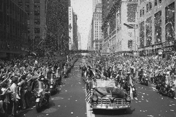 ADVANCE FOR USE SATURDAY, JULY 13, 2019 AND THEREAFTER-FILE - In this Aug. 13, 1969 file photo, people line 42nd Street in New York to cheer Apollo 11 astronauts, in lead car from left, Buzz Aldrin, Michael Collins and Neil Armstrong, traveling east on 42nd street, towards the United Nations. (AP Photo/File)