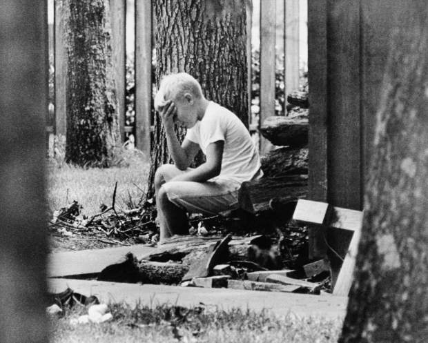 ADVANCE FOR USE SATURDAY, JULY 13, 2019 AND THEREAFTER-FILE - In this July 20, 1969 file photo, Andy Aldrin, 10, sits on a pile of cordwood in the backyard of his home in Houston while other members of his family listen to the reports of the progress of the Apollo II lunar module carrying his father, Col. Buzz Aldrin and fellow astronaut Neil Armstrong to a landing on the moon. (AP Photo)