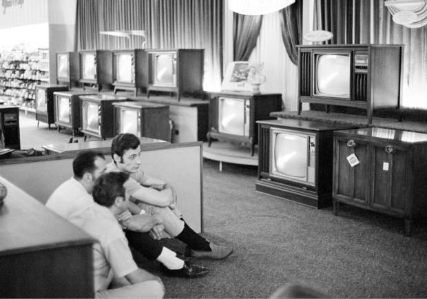 ADVANCE FOR USE SATURDAY, JULY 13, 2019 AND THEREAFTER-FILE - In this July 16, 1969 file photo, people watch the Apollo 11 Saturn V rocket launch on multiple TV's at a Sears department store in White Plains, N.Y. (AP Photo/Ron Frehm, File)