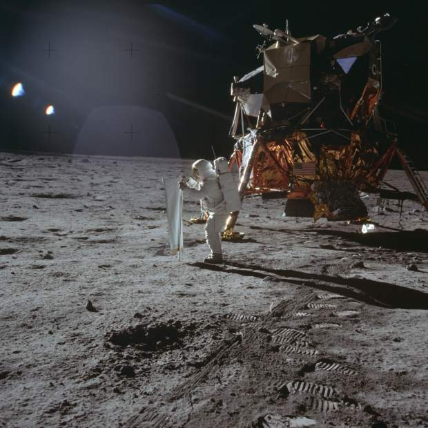 ADVANCE FOR USE SATURDAY, JULY 13, 2019 AND THEREAFTER-In this July 20, 1969 photo made available by NASA, Apollo 11 astronaut Buzz Aldrin works on a solar wind experiment device on the surface of the moon. (Neil Armstrong/NASA via AP)