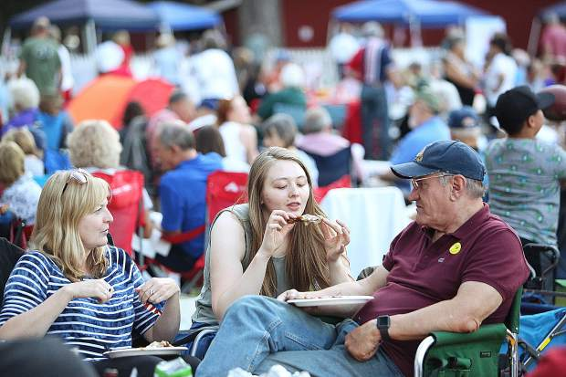 Anna Burch enjoys a piece of chicken along side mother Marsha Burch and Scott Browne prior to the start of Wednesday's Music in the Mountain Patriotic Pops Concert at the fairgrounds.