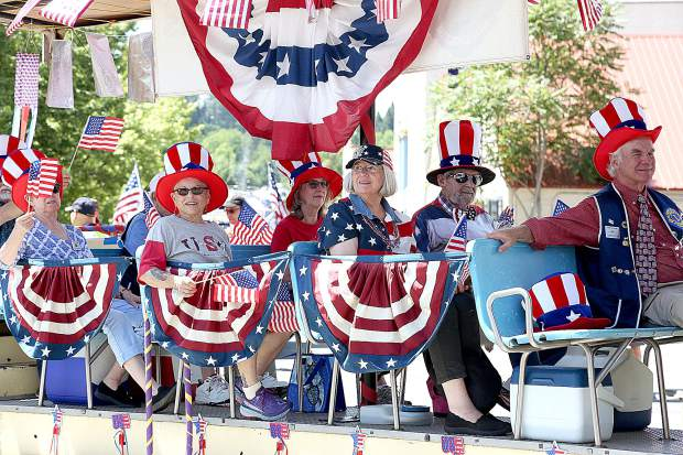 Members of the local Lions Club ride a float in festive