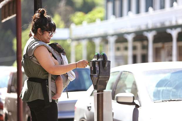 Downtown Nevada City business owner Lisa Rodriguez places a pair of quarters into the parking meter in front of her store Buho where she parked Wednesday morning. Rodriguez is concerned about the impacts to business owners and employees if the proposed parking rate increase is adopted.