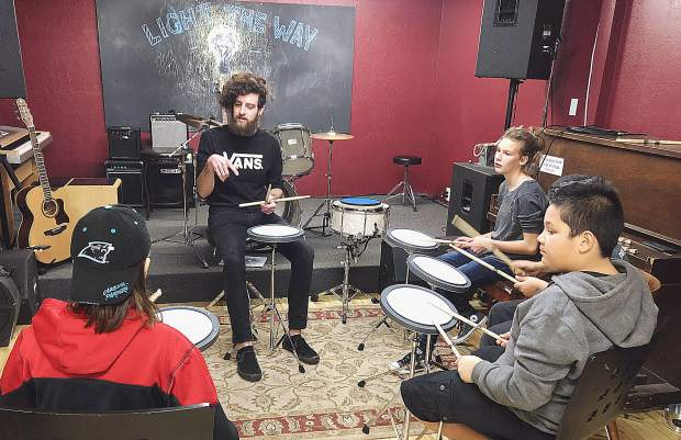 Local drumming instructor, Beau Askew, providing drumming lessons to middle school students. NEO provides a space for youth to congregate, learn from one another and bond.