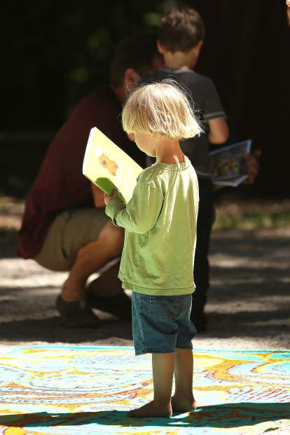 Three year old Elijah Hubbard holds a bilingual Potter the Otter cookbook that was given to him and the others in attendance of Saturday's Pop Up Library hosted by the Nevada County Community Library at Pioneer Park.