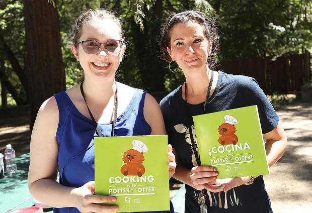 Nevada County Community Library employees Megan Lloyd (left) and Liza Alvarez hold English and Spanish versions of Cooking with Potter the Otter, that they read to kids during Saturday's Pop Up Library at Pioneer Park. After the story time, attendees were given copies of the book with bilingual text.