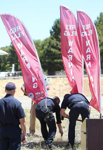 Firefighters work on staking a Ready Nevada County red flag warning flag into the ground, much as they would in front of a fire station during an actual red flag warning event.