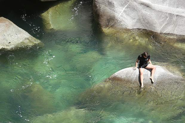A swimmer perches on a boulder in the middle of the South Yuba River near the Highway 49 bridge swimming hole on the Fourth of July. River levels have subsided but first responders warn of cold and swift moving currents that can pin or trap you if you're not careful.