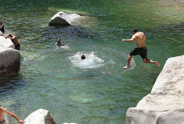 Swimmers jump into the waters of the South Yuba River at the Highway 49 bridge on the Fourth of July.