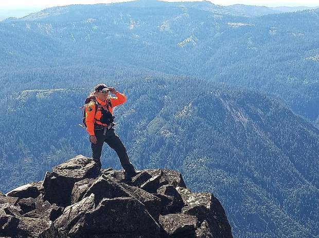 Search and Rescue team member Kim Blix surveys the rugged terrain during a training mission.