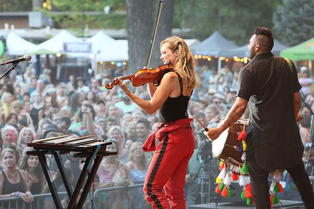 Members of the Canadian band Delhi 2 Dublin violinist Serena Eades and Ravi Binning on dhol, play their mixture of electronic, funk, dub, reggae, hip hop, Celtic, and Bhangra genres to much delight of the WorldFest crowd Saturday evening on the Meadow stage.
