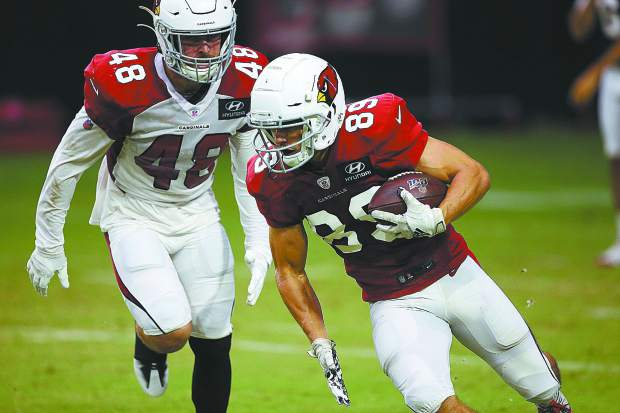 Arizona Cardinals wide receiver Andy Isabella (89) runs with the ball as Arizona Cardinals linebacker Tanner Vallejo (48) arrives for a tackle during an NFL football training camp practice Wednesday, July 31, 2019, in Glendale, Ariz. (AP Photo/Ross D. Franklin)