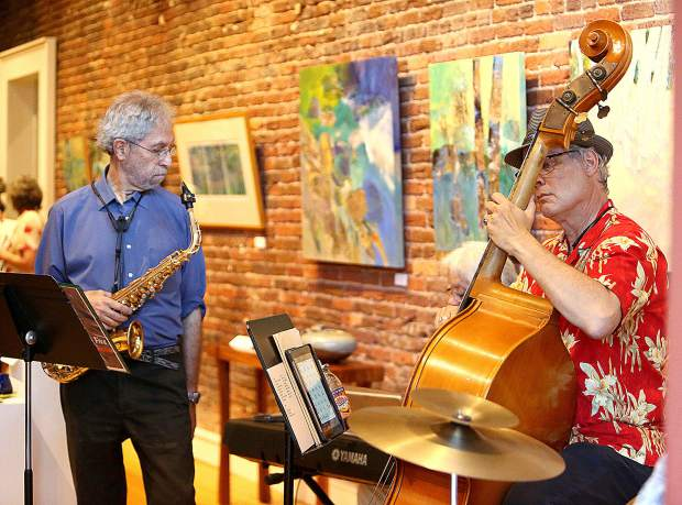 Musicians accompany 2 dimensional artwork on the walls inside of one of the many downtown Nevada City art galleries.