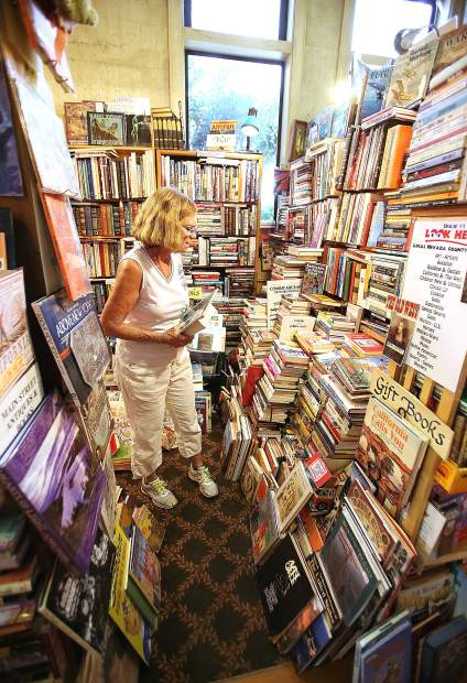 Marilyn Tubbs, one of Booktown Books' nine collectors, stands amidst her towering collection while preparing an exhibit for the 2019 Nevada County Fair earlier this month in downtown Grass Valley.