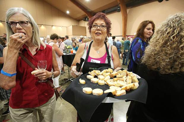 Bounty of the County volunteer Norma Moore walks around the event offering bread slices to accompany the area wine selections.