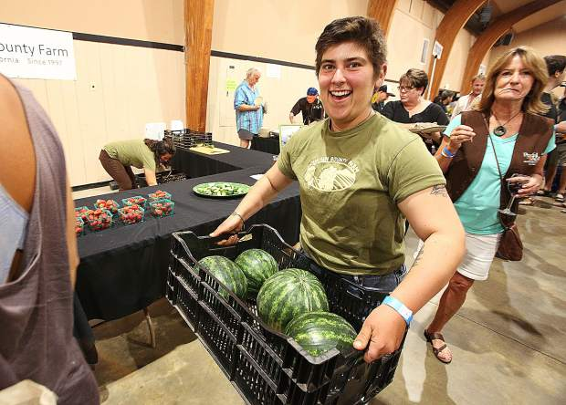 Mountain Bounty Farms' Gabrielle Amaya brings in a basket full of watermelons to be offered up at their Bounty of the County booth Wednesday at the Fairgrounds.