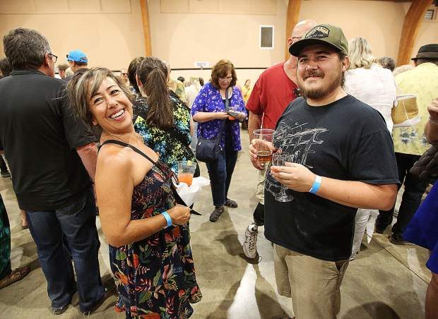Mother and son Tina Jackson and Tanner Collins smile as they wait in line for the Watershed at The Owl's Bounty of the County booth.