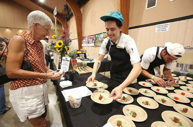 Chefs from The Stone House put together plates of compressed melon, cashew pudding with pickled Fresno peppers.