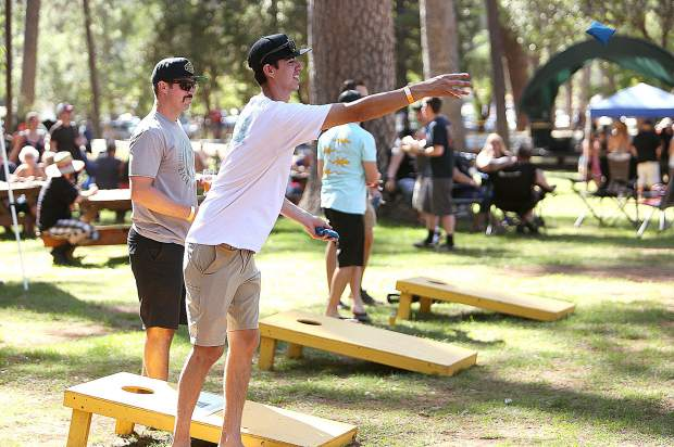 BrewFest goers take a toss at the corn hole games while music from the band Elevation plays on the stage behind.