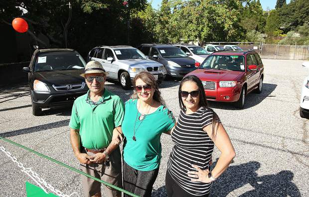 Mohsen Afshartabar, wife Afsaneh and daughter Roxy Wilson stand in front of their newest business venture, The Car Lot GV, located on East Main Street in Grass Valley.