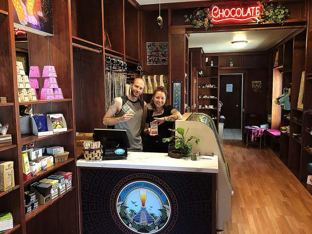 Ariel Augusto Wolansky and Lauren Brown highlight some of the chocolate products they sell at Choquiero. The two hope to eventually sell vegan-only products.