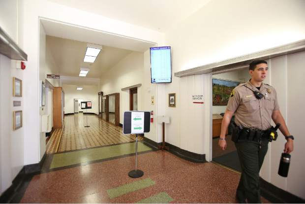 A Nevada County sheriff's deputy walks the first floor of the Nevada County Courthouse Thursday afternoon.