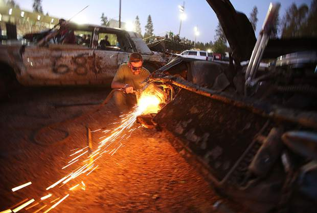 Everyday people become motor car pit crew members as Auburn's Austin White demonstrates while using a torch to cut away fenders that can get in the way and cause flats when hit by other vehicles in the arena.