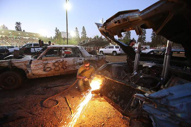 Auburn's Austin White uses an acetylene torch to cut away fenders from a 1979 Lincoln Continental driven by Louis Gray in Sunday night's destruction derby at the Nevada County Fair. Cutting away fenders and other excess parts is one technique that derby pit crew members use to help their cars' chances in the arena.