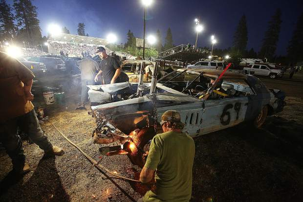 Pit crew members work on the 1979 Lincoln Continental driven by Louis Gray in between heats at the Nevada County Fair.