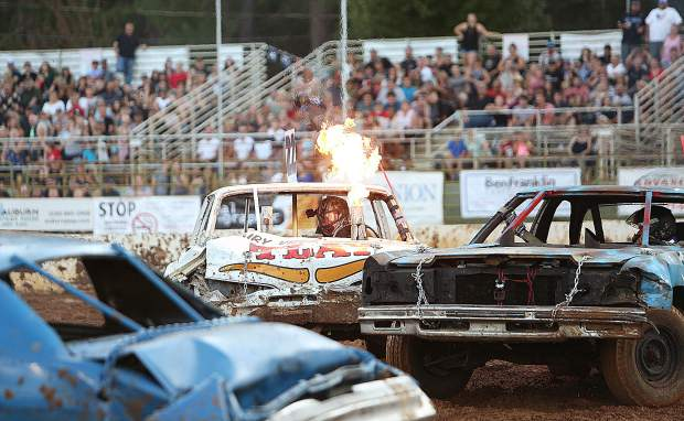 Flames leap from the exhaust of destruction derby driver Clarence Oliveira's 67 Dodge Monarch while smashing through his competition at the Nevada County Fair arena for the annual end of fair spectacle Sunday night.