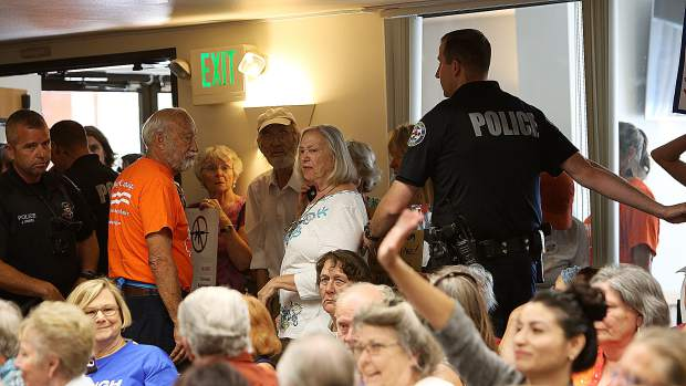 An unruly crowd member is escorted out of a town hall meeting hosted by Congressman Doug LaMalfa earlier this month at Grass Valley City Hall.