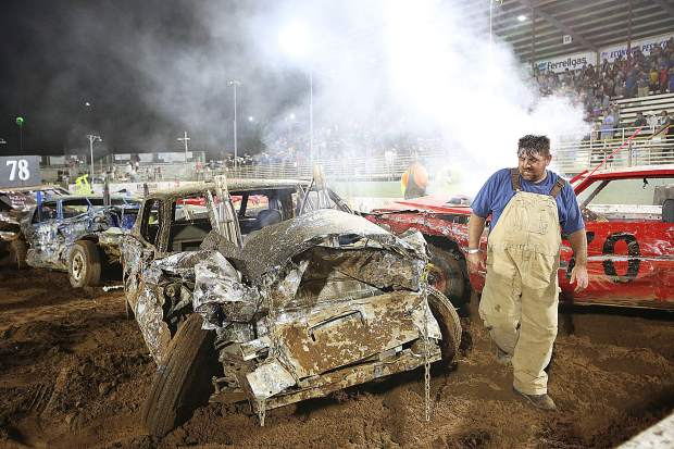 A destruction derby driver walks to inspect the front of his car after the final heat of competition during the final night of the Nevada County Fair.
