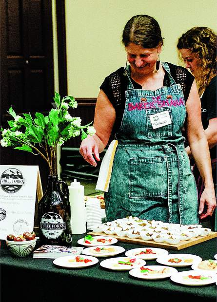 Shana Maziarz, co-owner of Three Forks Bakery & Brewery prepares samples for Bounty of the County.