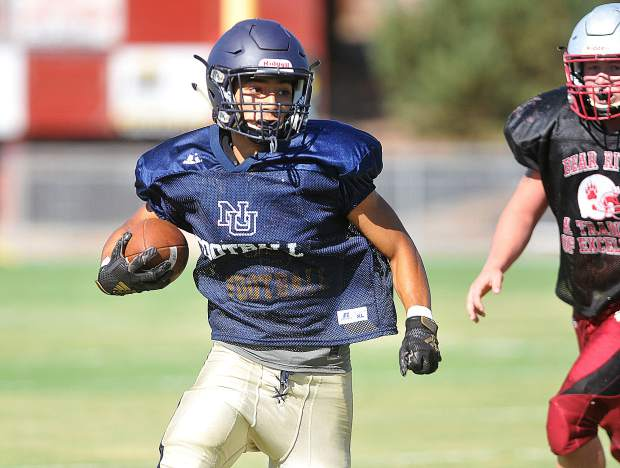 An NU player carries the ball down the field for the Miners during Saturday's scrimmage against the Bear River Bruins.